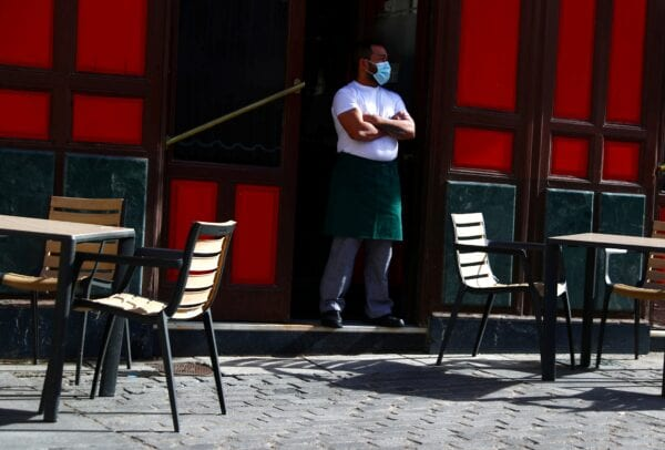 A waiter wearing a protective nose and mouth mask waits for customers